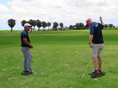 Glen Beaver provides feedback to golf student as they complete one-handed golf swing.