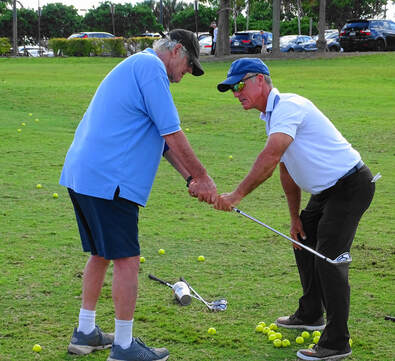 Glen Beaver correcting club position during golf lesson.